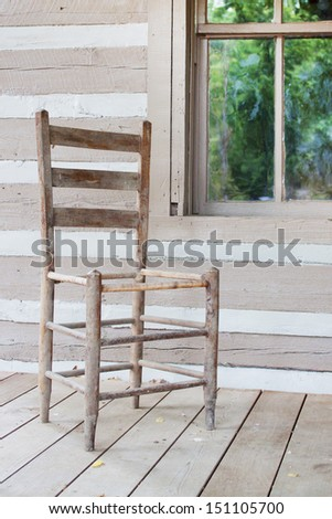 Old chair on a porch of a century-old house - stock photo