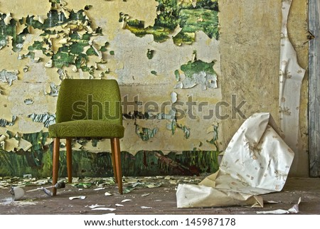 Old chair stands in front of a flaked off wall - stock photo