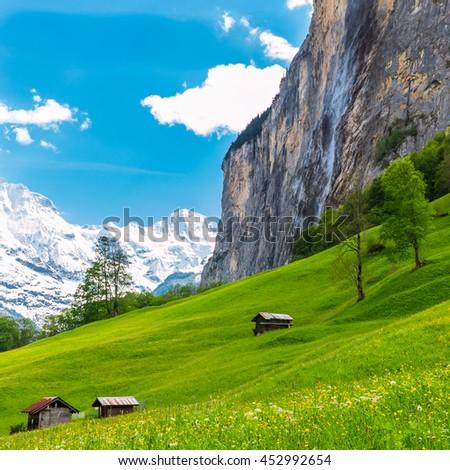 Old chalets on green mountain slope. Swiss Alps. Lauterbrunnen, Switzerland, Europe. - stock photo