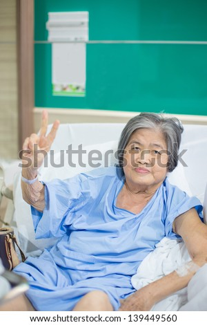 Old cheerful asian granny admitted in hospital holding up 2 fingers sign of courage and will to fight - stock photo