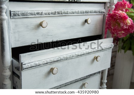 Old chest of drawers with an extended box and flowers - stock photo