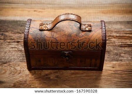 Old chest on wooden table - stock photo