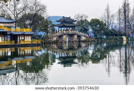 Old Chinese Bridge to Quyuan Garden Yellow Boat West Lake Hangzhou Reflection Zhejiang China .  - stock photo