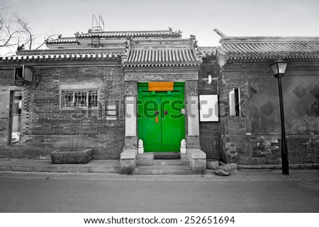 Old Chinese house with brightly colored green door (Beijing hutong house)  - stock photo