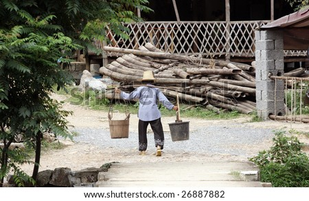 Old Chinese women carrying two buckets of water - stock photo