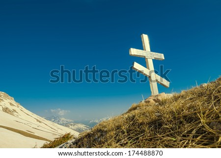 old christian cross on a hill slope - stock photo