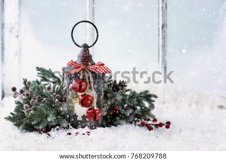 Old Christmas lantern with pine tree branches sitting on a snowy window ledge.