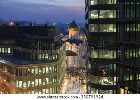 Old church between two office buildings and walking people in evening Moscow - stock photo