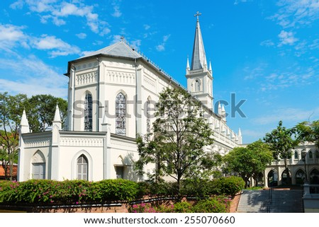 Old church building in neoclassical style with stained-glass window under blue sky. - stock photo