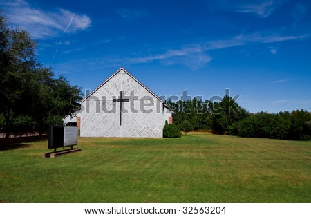 Old church in large field with empty sign and cross on side of building