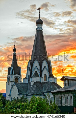 Old church over burning sunset in russian village