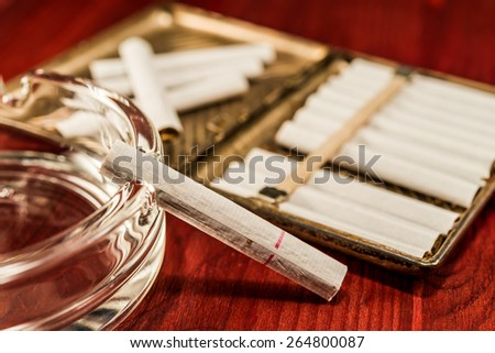 Old cigarette case with cigarettes and glass ashtray on a table in mahogany