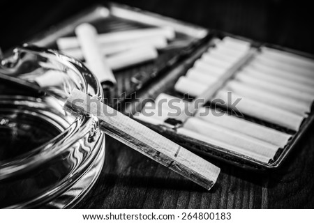 Old cigarette case with cigarettes and glass ashtray on a table in mahogany. Image vignetting and black and white tones