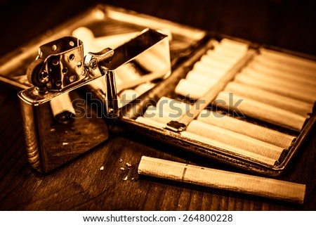 Old cigarette case with cigarettes and lighter on a table in mahogany. Focus on the cigarette, image vignetting and the yellow-orange toning - stock photo