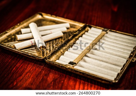 Old cigarette case with cigarettes on a table in mahogany. Image vignetting  - stock photo