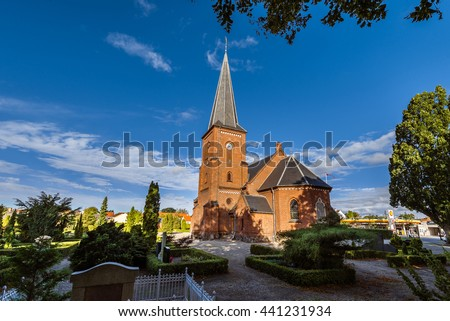 Old city cemetary and catholic church in Dragor, Denmark - September, 21th, 2015. Gravestones, greenery and cloud sky at the early morning in fishman village near Copenhagen.