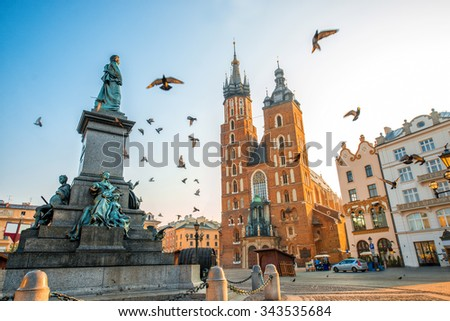 Old city center view with Adam Mickiewicz monument, St. Mary's Basilica and birds flying in Krakow on the morning - stock photo