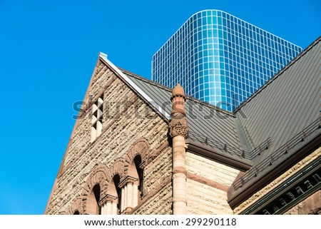 Old City Hall contrasts against a modern skyscraper - stock photo