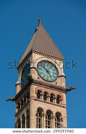Old city hall tower with clock, zoomed in against a backdrop of a  a bright blue sky - stock photo