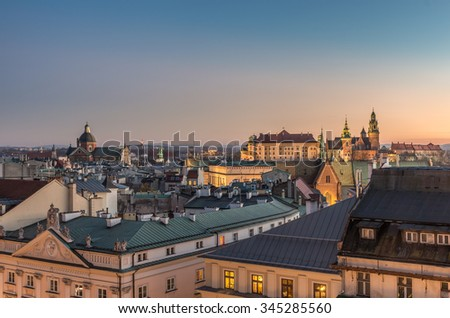 Old city, royal castle and cathedral on the Wawel hill seen from the Town Hall tower in Krakow, Poland in the evening - stock photo