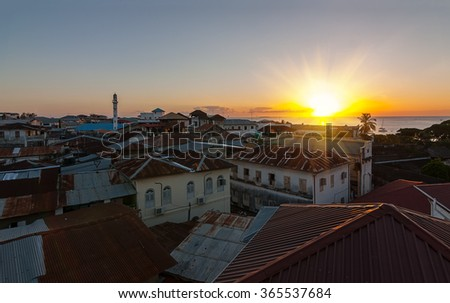 old city skyline view over buildings and iron roof tops looking at the tropical sun setting - stock photo