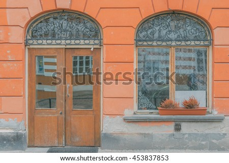 Old city vintage elements. Rounded decorated door with rounded window on a orange building  facade wall. Historical city elements. Classic european architecture. Luxury estate rent sale concept.