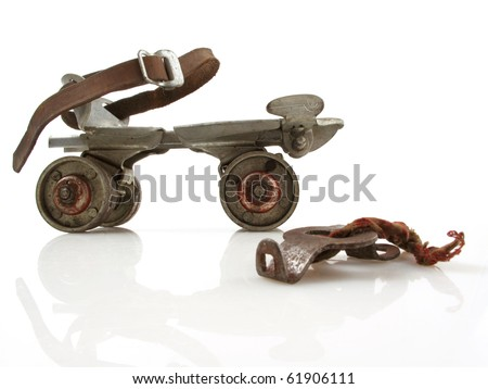 Old clamp-on roller skate with adjustment key on white - stock photo
