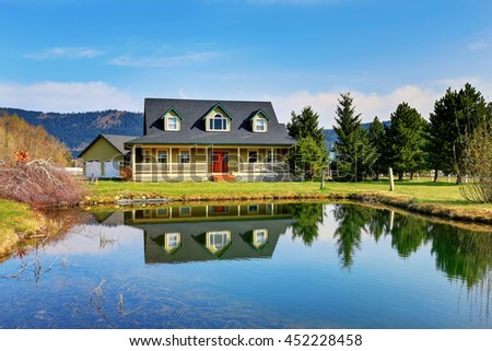 Old classic American green house with porch and garage. View from the water - stock photo