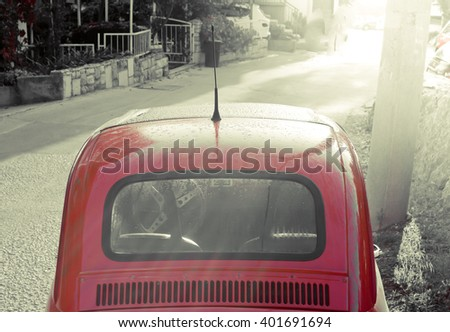 Old classic car with sun rays in background, summer morning in narrow city street. / Summer morning. / Toned photography. - stock photo