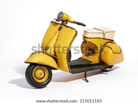 Old classic vintage yellow motor scooter with a wide foot board and saddle style seat standing upright on its stand on a white background