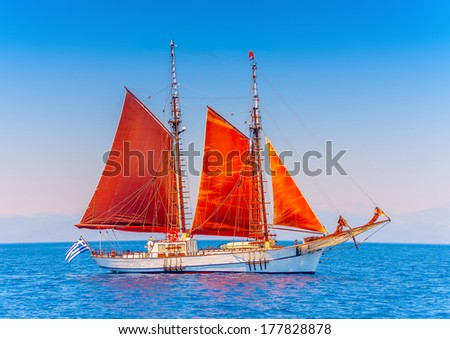 Old classic wooden boat with red sails, during a Classic Boats Regatta in Spetses island in Greece - stock photo