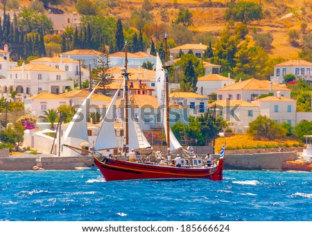 Old classic wooden red Greek boat (type Perama) with sails during a Classic Boats Regatta in Spetses island in Greece - stock photo