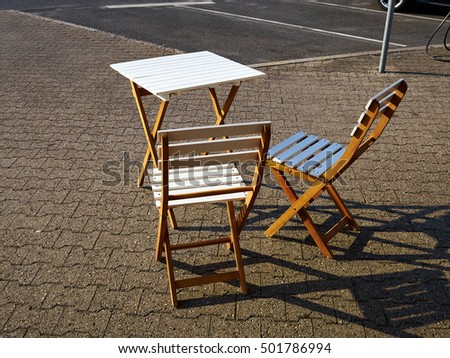 Old classical vintage style wooden coffee table and chairs in a street