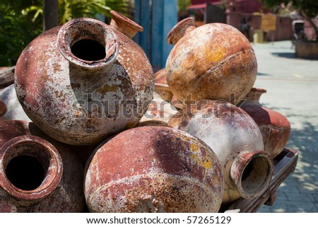 Old clay amphoras piled on the cart. Shallow depth of field. - stock photo