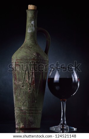 Old clay bottle of wine and glass. - stock photo