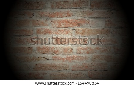 Old clay bricks wall with spotlight - stock photo