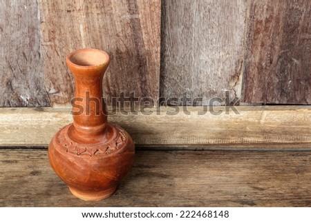 Old clay ceramic vase, Old clay ceramic vase in wooden background. - stock photo