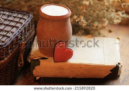 old clay jug of milk, dry food health daisy flowers book heart love romantic Valentine breakfast - stock photo