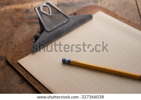 Old clipboard and a pencil, on old grungy wooden table. - stock photo