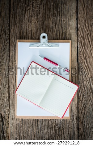 Old clipboard, red notebook, red pen on grungy wooden surface, with plenty of copy space.Photo retro style