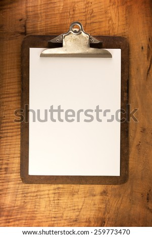 Old clipboard with an blank pieces of paper, on old beautifully figured wooden surface. Intentionally shot with low key shadows. - stock photo
