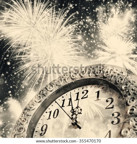 Old clock at twelve o'clock with fireworks and holiday lights - New Year's at midnight - stock photo