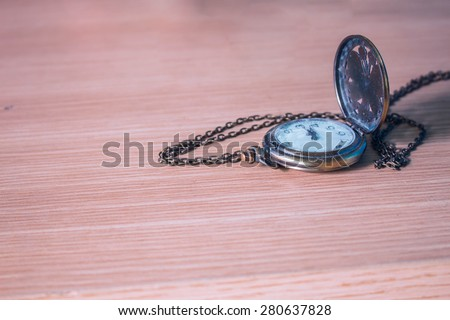 Old clock on a wooden table - stock photo