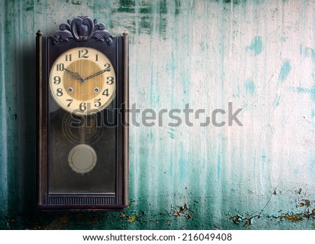 Old clock on grunge wall.