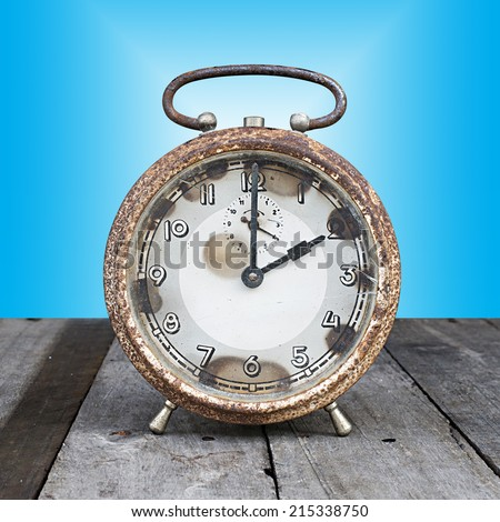 Old clock set on a wooden plate with a blue background - stock photo