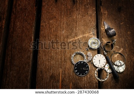 Old clock, spare parts and repair tools on a wooden background.