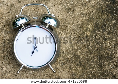 Old clock with no number of time on cement floor