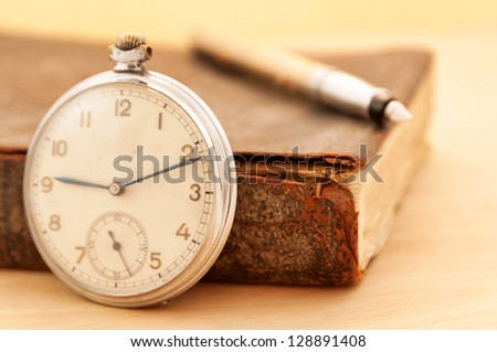 Old clock with vintage book - stock photo