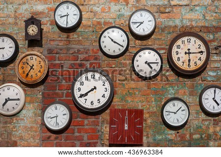 Old clocks  on brick wall - stock photo