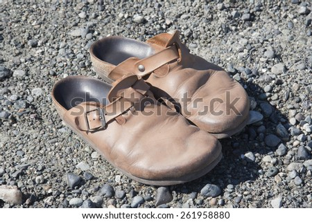 Old Clogs on Rocks  - stock photo